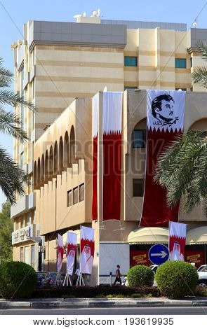 DOHA, QATAR - JULY 1, 2017: Qatari flags emblazoned with images of Emir Tamim bin Hamad al-Thani fly from a department store in the Emirate's capital as the country faces a siege from its neighbours
