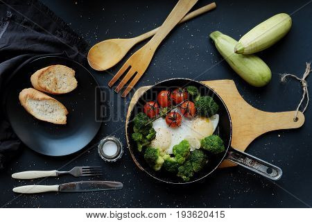 Fried eggs with broccoli and cherry tomatoes in a frying pan on a dark background