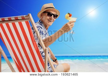 Mature man with a cocktail sitting in a deck chair on a beach