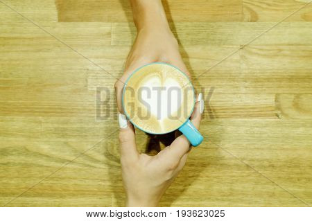 Cappuccino With Heart Froth Between Two Hands On Wooden Table. Human Pastime