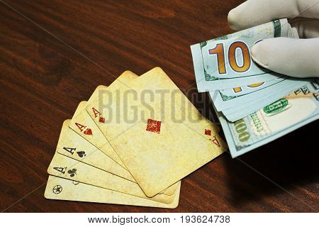 Poker bet or gain holding in a hand in glove over the table with playing cards