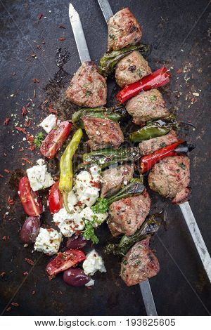 Traditional Greek Souvlaki with Feta and Vegetable as top view on an old rusty metal sheet