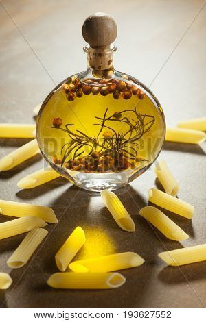 Bottle Extra Virgin Olive Oil With Spices And Some Pices Of Pasta On A Ceramic Background