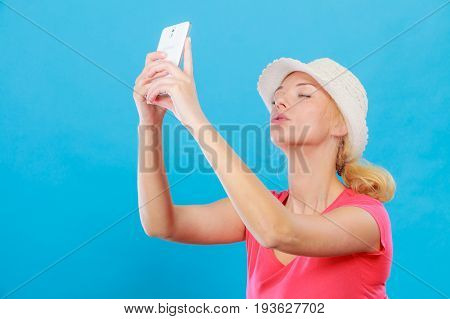 Technology modern photography confidence conept. Happy attractive adult blonde woman in sun hat taking picture of herself with smartphone selfie.