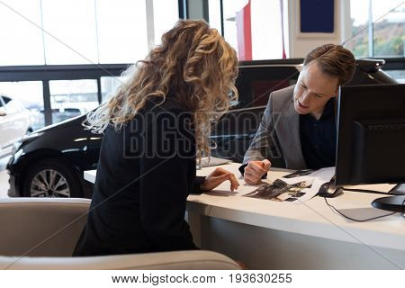 Salesman showing document to customer while sitting at desk in car showroom