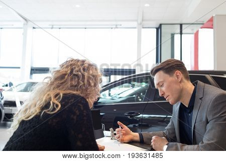 Salesman discussing over document with customer whiel sitting at desk in car showroom