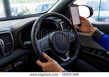 Cropped image of woman using phone during test drive while sitting in car
