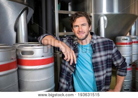 Portrait of confident worker standing by kegs at warehouse