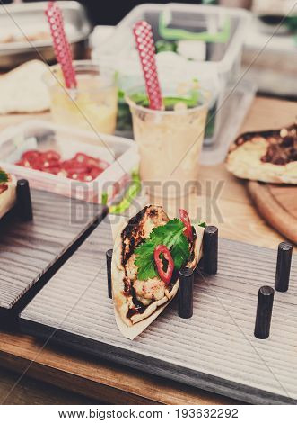 Street vendor selling taco outdoors. Mexican cuisine snacks closeup, wrapped in craft paper. Fast food for commercial kitchen.