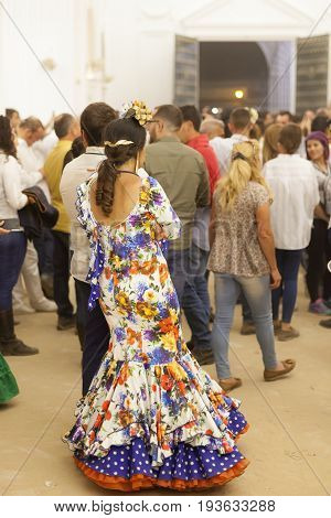 El Rocio Spain - June 2 2017: Female pilgrim in traditional spanish flamenco dress in the hermitage of El Rocio during the Romeria 2017. Andalusia Spain