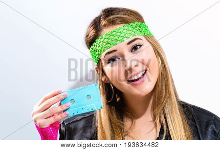 Woman in 1980's fashion holding a cassette tape on a white background