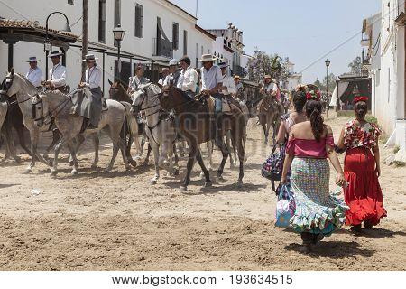 El Rocio Spain - June 2 2017: Group of pilgrims on horseback in traditional spanish dress in El Rocio during the Romeria 2017. Province of Huelva Almonte Andalusia Spain