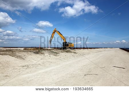 Excavator works on a construction site with excavation
