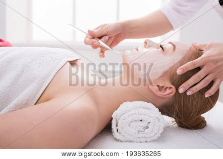 Apply face mask, spa beauty treatment and skincare. Woman getting facial nourishing mask by beautician at spa salon, close-up