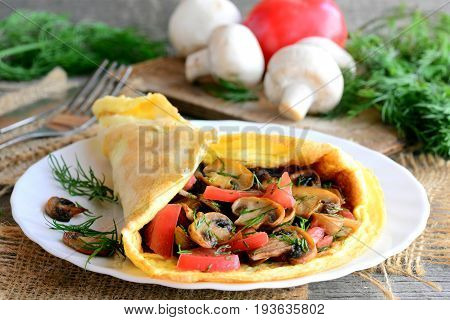 Ruddy omelet stuffed with fried mushrooms, fresh tomato slices and dill herbs. Home stuffed omelet on a plate. Rustic style