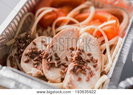 Healthy lunch in foil container. Healthy food take away and delivery. Durum wheat pasta, steamed turkey, fresh vegetables and flax seeds in box on white background, closeup