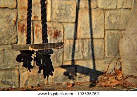 Wooden swing whit black ropes on the wall, closeup photography