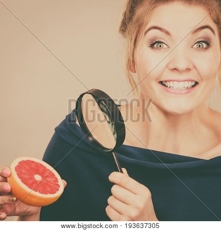 Woman Holding Magniferlooking Grapefruit