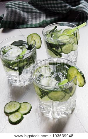 Fresh cold water with lemon, cucumber, ginger, mint and ice in a pitcher and glass on a tray