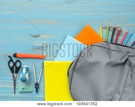 School backpack on blue wooden background