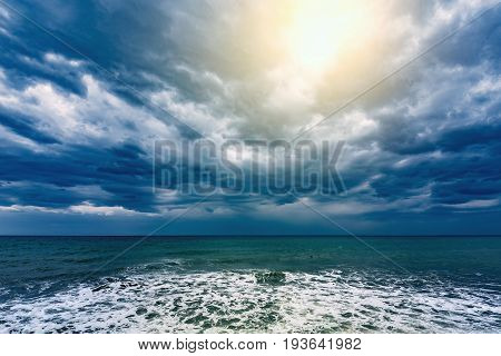 Dark stormy sky and sunlight above the ocean surface