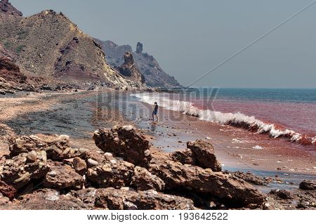 Hormuz Island Hormozgan Province Iran - 17 april 2017: Iranian Island of Hormuz in Persian Gulf A lone traveler walks on the red beach along the surf line.