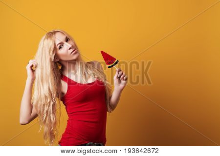 Blondy Girl Holding Big Candy Looking At Camera Isolated Over Yellow Background.