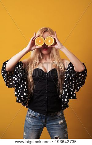 Happy Young Woman Holding Halvesof Oranges Isolated Over Yellow Background.
