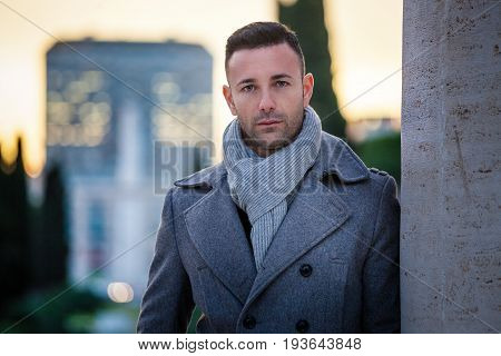 Handsome modern man in the city. Winter men fashion. A beautiful man with winter coat in the city. Behind him a cityscape with buildings and trees