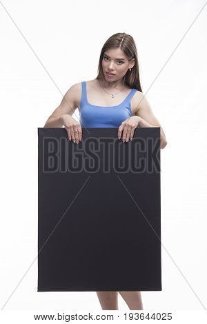 Young enigmatic woman portrait of a confident businesswoman showing presentation, pointing placard black background. Ideal for banners, registration forms, presentation, landings, presenting concept.