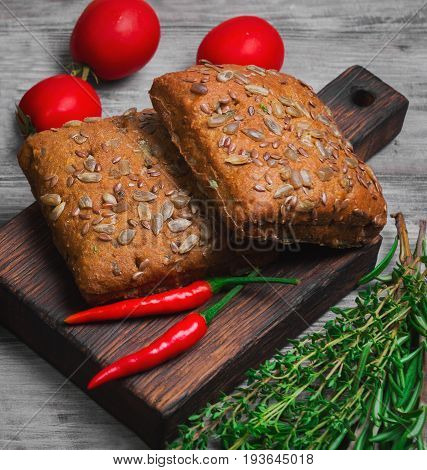 Whole grain fresh cereals bread buns with sunflower Sesame linen seeds. Spices for grain cereals bread buns tomatoes peppers rosemary thyme. Light white wooden background.