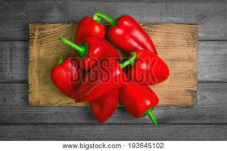 Heap Fresh red Bulgarian pepper on a gray rustic wooden background. Cutting board for red bell pepper. Top view blank space.