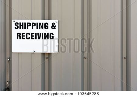 Shipping and Receiving sign on an steel panelled wall.