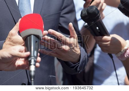 Press interview with business person or politician. News conference.