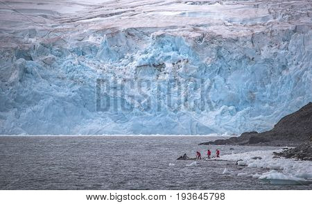 Tourists go to a rubber boat on ice and rocks. The bay is surrounded by an iceberg. Two people in red winter suits go to the boat. One man holds on to the boat standing on the shore. The driver of a rubber boat sits and looks at a group of tourists.