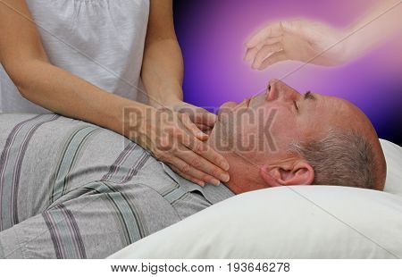 Spiritual help during a healing session - female hands laid either side of a male patient's throat channeling energy together with the help of a higher power on a dark purple background