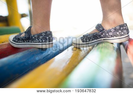 Low section of girl wearing shoes walking on jungle gym
