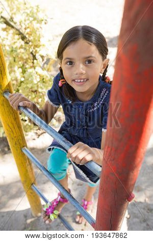 High angle portrait of happy girl climbing ladder of jungle gym