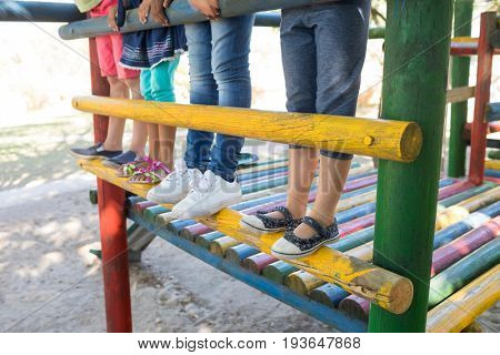 Low section of children standing on jungle gym at playground