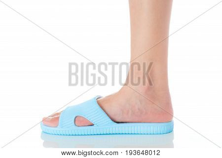 Woman foot wearing beautiful blue sandal standing with side view on white background Fashion woman concept.