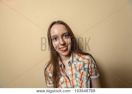 Emotional Portrait Of Funny Young Cute White Girl In Plaid Shirt Opposite Sienna Background.