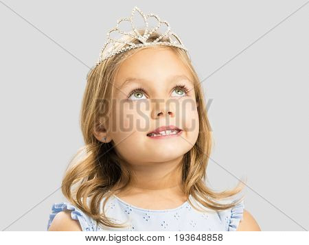 Portrait of a cute little girl wearing a princess crown and making a dreamy face