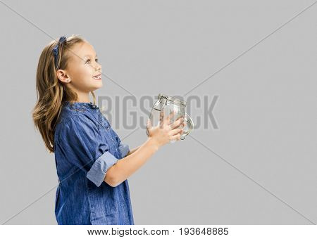 Cute girl holding a glass pot and release something