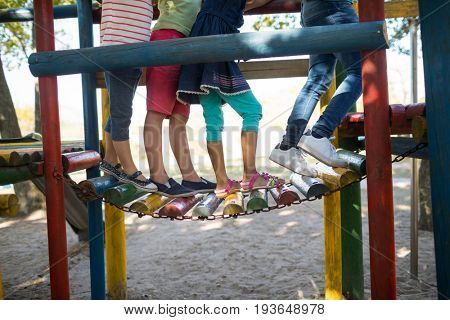 Low section of children walking on jungle gym at play ground