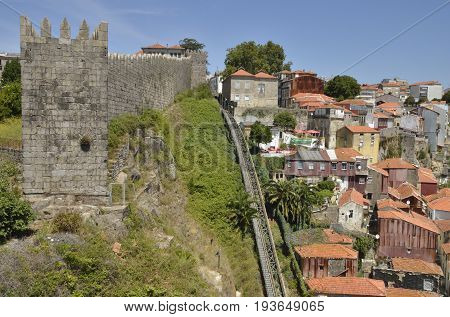 PORTO, PORTUGAL - AUGUST 7, 2015: Funicular tracks along the historical wall of Freiras over a steep cliff in the old town of Porto Portugal.