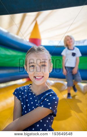 Portrait of girl sitting on bouncy castle while brother playing in background