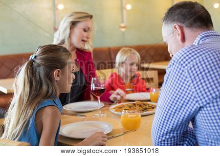 Family talking while enjoying appetizer at table in restaurant