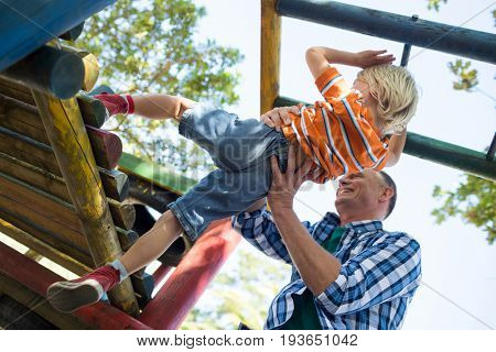Low angle view of father assisting son in playing on jungle gym at playground