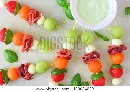 Summer Fruit Skewers With Melon, Cheese And Prosciutto, Above View On A White Marble Background