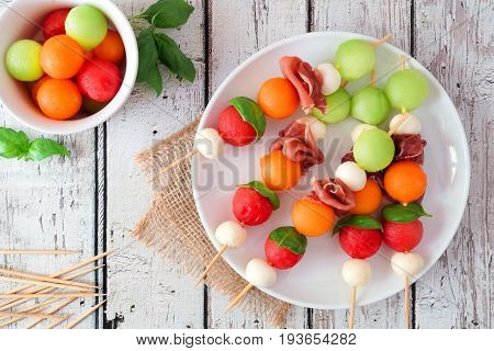 Plate Of Delicious Summer Fruit Skewers With Melon, Cheese And Prosciutto On A Rustic White Wood Bac